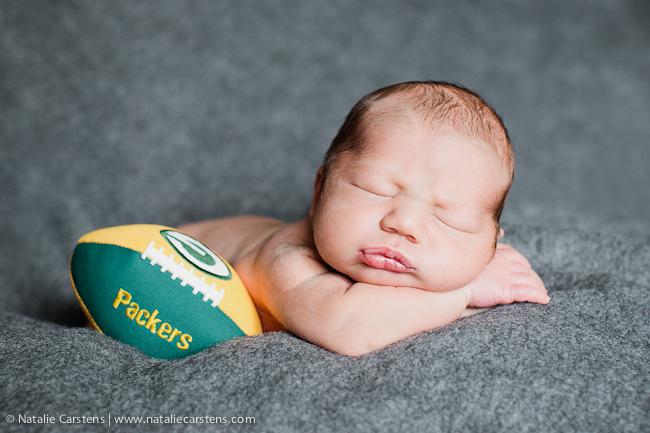 newborn baby boy, sleeping with Packers' football | Natalie Carstens, The Birth Photographer