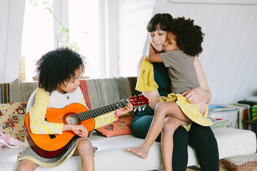 a mother with her daughters, one girl playing a guitar while the other one hugs her mama | Photographer: Natalie Carstens, nataliecarstens.com