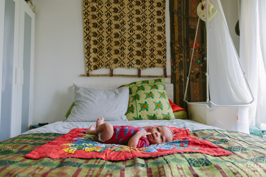 a newborn baby boy laying on a big bed | Photographer: Natalie Carstens, nataliecarstens.com