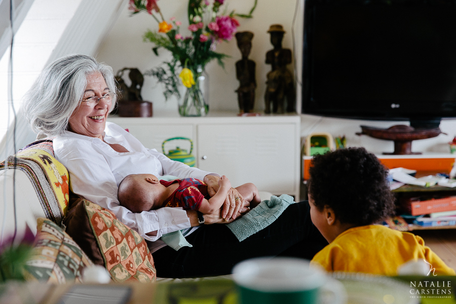 grandma is on the sofa holding her baby grandson and looking towards another of her grandchildren with a big smile on her face | Photographer: Natalie Carstens, nataliecarstens.com