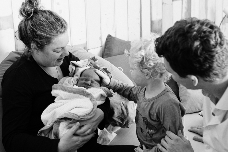 First moments at home after hospital birth. A big sister meets her baby brother for the first time. The Hague. | Birth Story Photography by Natalie Carstens #nataliecarstensphotographer #birth #childbirth #labour #hospitalbirth #hagaziekenhuis #denhaag #geboorte