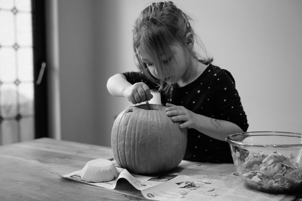 Little girl carving a pumpkin for halloween