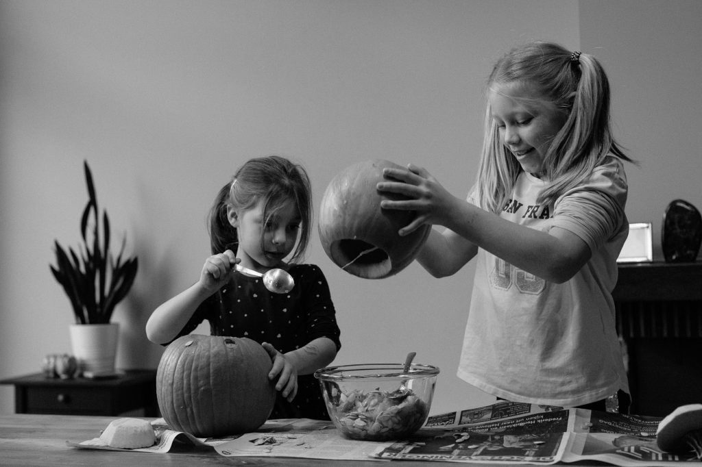 Two sisters carving pumpkins for halloween