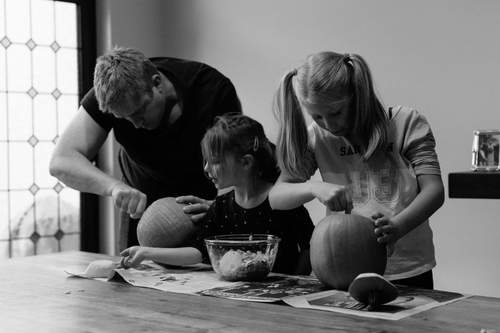 Father and daughters carving pumpkins for halloween