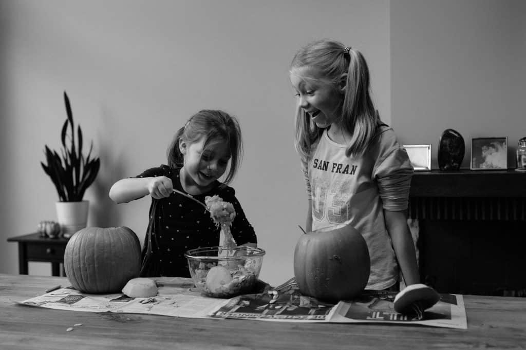 Sisters carving pumpkins for halloween