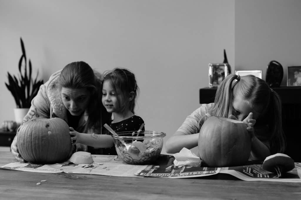 Mother and daughters drawing faces on pumpkins for halloween