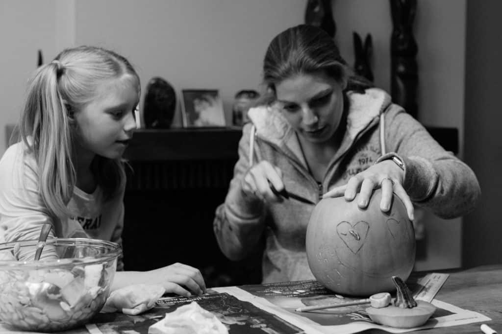 Mother carving an owl on a pumpkin for halloween