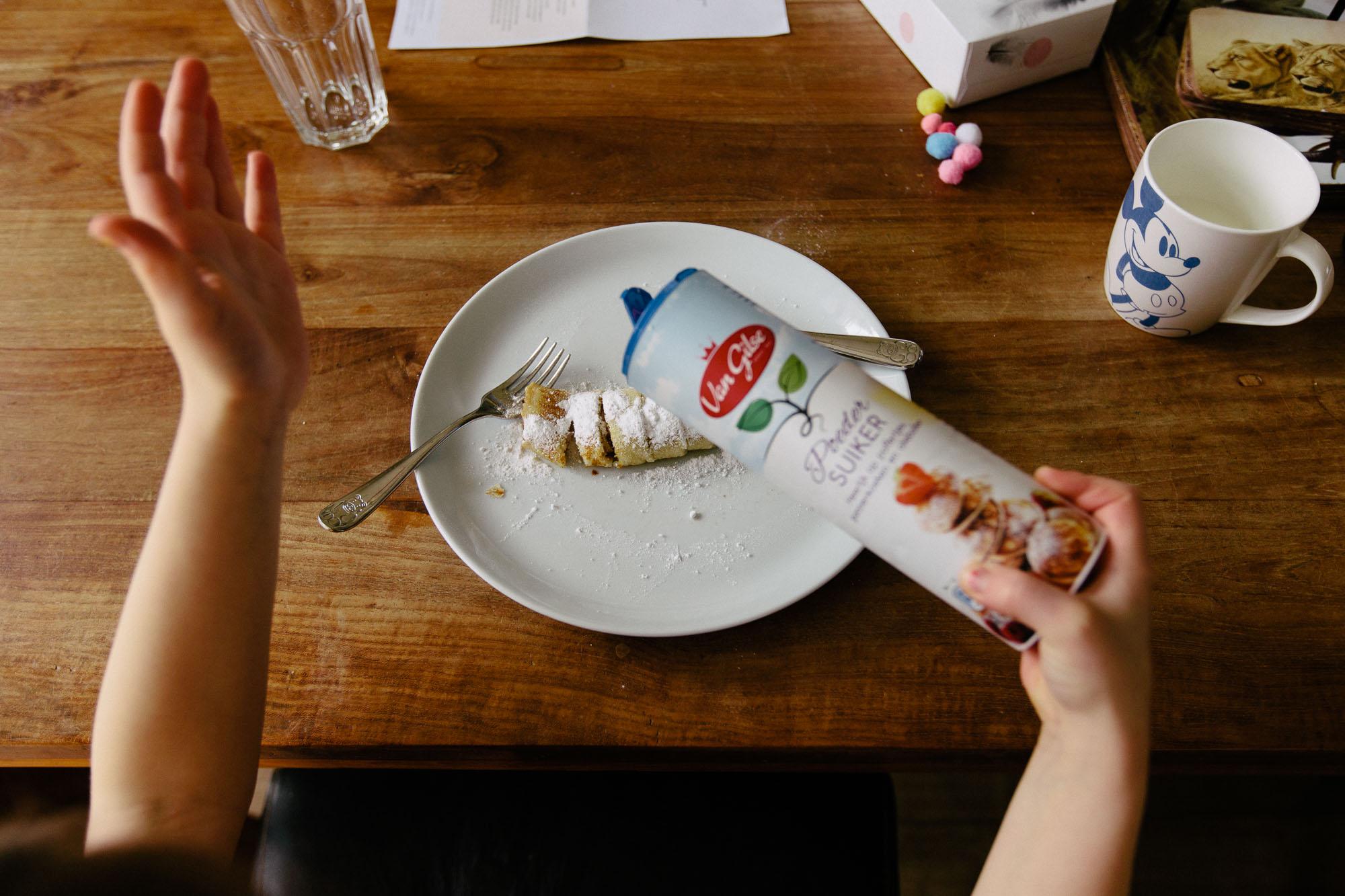 child adding sugar to pancakes