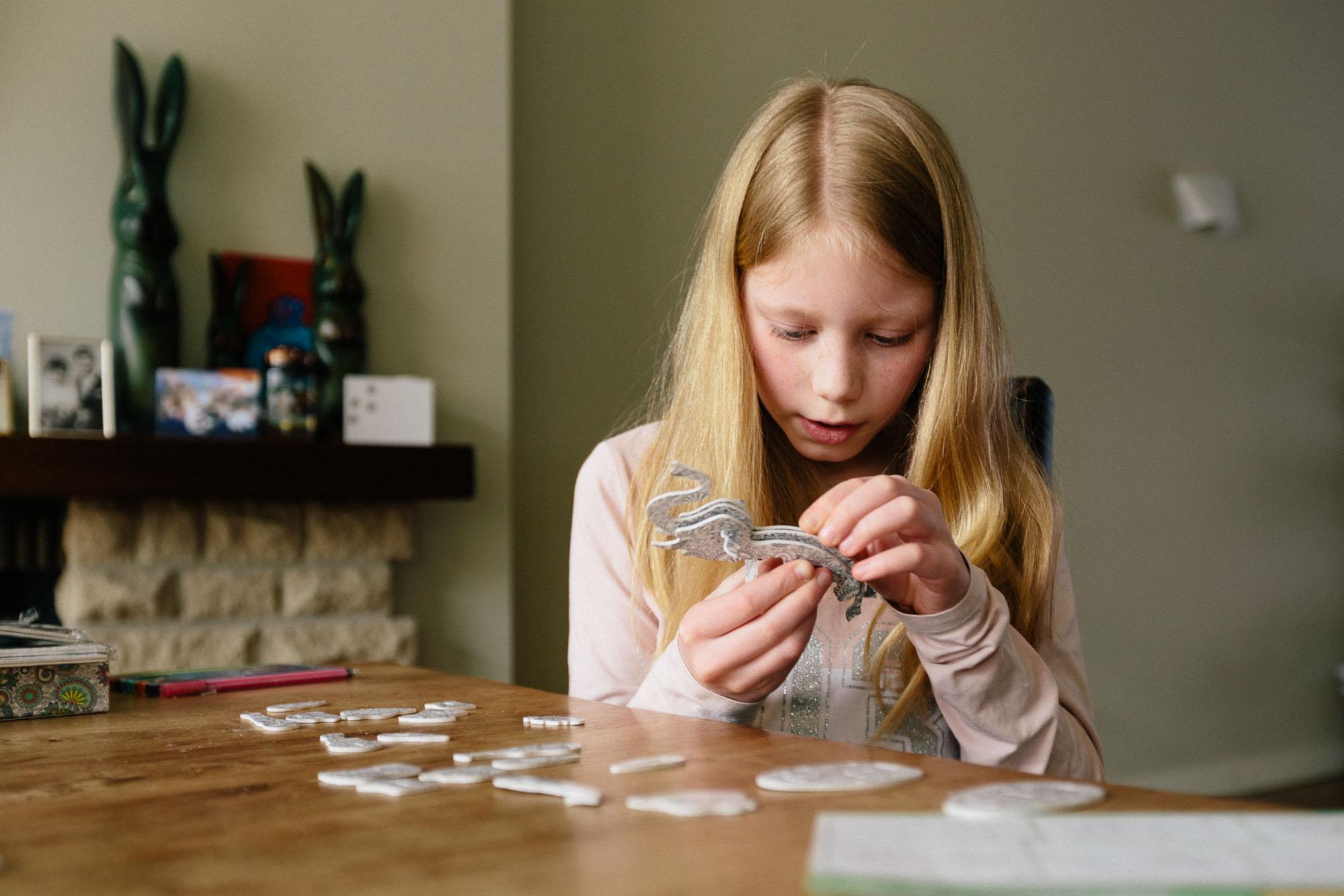 child constructing cardboard animals