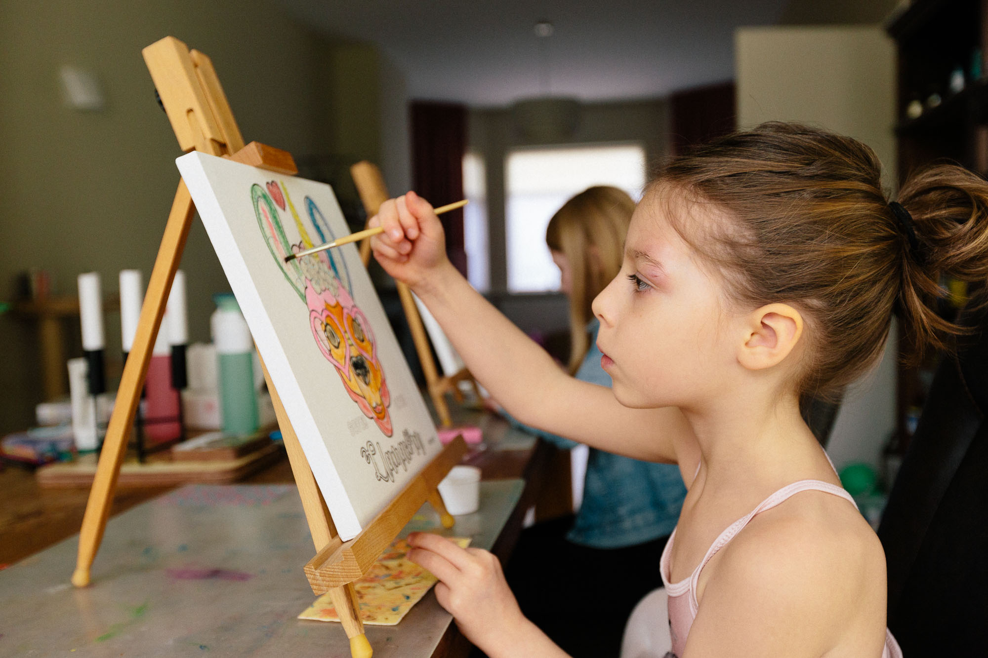 child painting a canvas on an easel